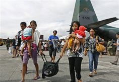 Survivors from Tacloban, which was devastated by Typhoon Haiyan disembark a Philippine Air Force C-130 aircraft at the Villamor Airbase, Tuesday, Nov. 12, 2013, in Manila, Philippines. Authorities said at least 9.7 million people in 41 provinces were affected by the typhoon, which was likely the deadliest natural disaster to beset this poor Southeast Asian nation. (AP Photo/Vincent Yu)