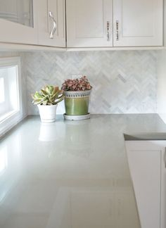 White cabinets with marble herringbone backsplash and sage green quartz countert. White cabinets with marble herringbone backsplash and sage green quartz countertops Quartz Backsplash, White Kitchen Backsplash, Herringbone Backsplash, White Kitchen Cabinets, Kitchen Redo, Kitchen Tiles, New Kitchen, Awesome Kitchen, Backsplash Design