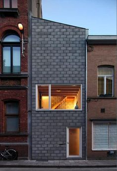 A long, narrow, massively concrete family home in the heart of Ghent, Belgium, snugly fits between two buildings.
