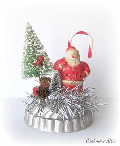 Vintage Inspired Christmas Ornament This charming Santa decoration was handmade. He stands atop vintage tinsel on an old tin tart mold. An old plastic candy cane sweetens up the decoration. Two bottle brush trees and a small pinecone are nestled by his side. A tiny cardinal has landed in the tree to get a better look at Santa. This is constructed with all original vintage pieces and there may be age appropriate flaws. The piece stands 5-1/2 tall and 3-3/4 wide