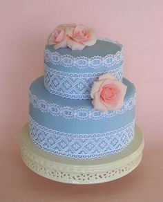 delightful two tiered cake ... baby blue ... intricate white lace wraps around the layers ... gorgeous pink roses nestle on the tops ...