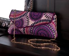 The colorful embroidery on this asymmetrical clutch and shimmering detachable gold chain make it perfect for daytime use and those special evening occasions.