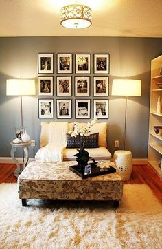 Gorgeous living room design with blue gray walls paint color, tan sofa settee, floral rectangular ottoman, gray table, polished chrome floor lamps, flokati rug, white garden stool, bookcase and black & white photo gallery.