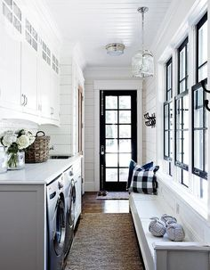 Galley style laundry room with side by side silver front load washer and dryer below a white counter which highlights an undermount stainless steel sink alongside shiplap clad walls with white shaker cabinets above accented with white scalloped trim. A distressed white bench stands across from the washer and dyer topped with gray nautical rope decor and navy buffalo check pillows below black framed windows lit by a Small Arch