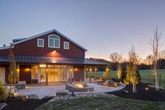 Red Party Barn Exterior With Back Patio With Square Fire Pit Barnwood Builders, Country Patio, Natural Stone Fireplaces, Fire Pit Landscaping, Square Fire Pit, Cool Fire Pits, Back Patio, Hgtv, Short Trees