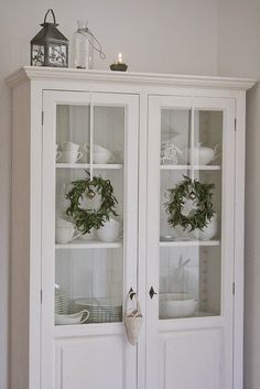 Love the tiny wreaths on this cupboard!