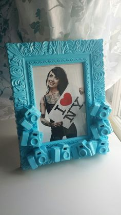 Bright blue picture frame, featuring nurmerous cameras a top one another. Frame measures 7.5 by 9.5 inches, and holds a 4.25 by 6 inch image. Hand