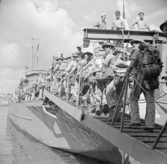 Troops board a landing craft at Catania, Sicily.
