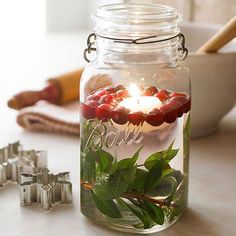 Add natural elements to your holiday decor for a rustic feel to your Christmas decorating. To make, place a leafy branch at the bottom of a large glass Mason jar or vase. Fill two-thirds full with water; drop in cranberries and a floating candle./