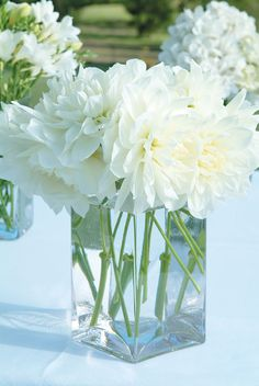 SIMPLE & PRETTY. Simple Glass Rectangular Vases of white flowers decorate the wedding ceremony table. #weddings #YourEventSolution