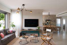 בסלון משחק בין גוונים של גרייז' (אפור-בז'), תכולים ועץ. מלבד הספה יש שני כסאות במאים ושולחנות עגולים שדינה עיצבה מרגלי ברזל ומחלקן העליון של חביות יין (צילום: גדעון לוין)