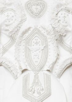 Embellished dress detail with ornate patterns & white textures; couture embroidery; close up fashion // Givenchy