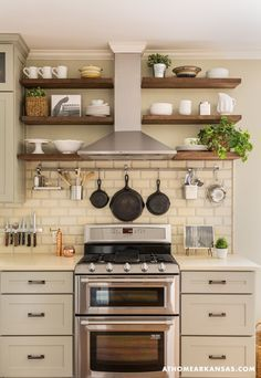 rustic white & gray kitchen with small stove, exposed wood shelves & hood