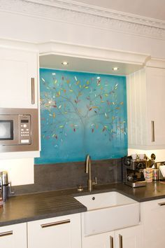 This splashback in Bromley, Kent, was done for one of our clients who really liked two of our tree designs, but wanted equal parts of each to be put into his design. As everything we make is bespoke, the client highlighted exactly what they wanted and the result is as you see below. The blue colours mix well with the branching leaves of the tree, creating a majestic and tall giant that really is a talking point for the room!