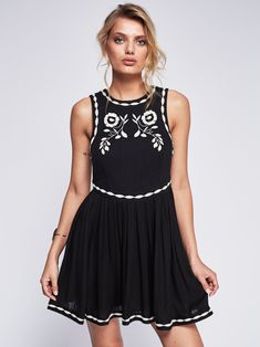 In a sleeveless silhouette this ethereal mini dress features beautiful embroidery with a full skirt and pleat detailing. Keyhole opening in back with a button closure.