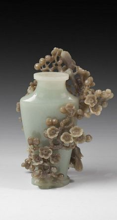 A carved jade bottle decorated with carving of magpie perching on blooming plum trees, all of natural colors and carved out of a single piece of jade stone.