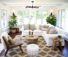 Contemporary eclectic design, white Interior, patterned rug, wood furnishings, upholstered seating, pendant lighting