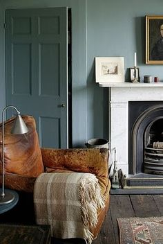 Old leather arm chair in period room painted in duck egg blue