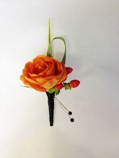 Small boutonniere of an orange spray rose with hypericum and lily grass by Seasonal Celebrations. Perfect for a ring bear or junior groomsmen. http://www.seasonalcelebrations.com