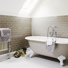 Sweet claw-foot soaking tub tucked into the eaves of a soothing, two-tone bath. | Photo: Brent Darby/IPC Images | thisoldhouse.com