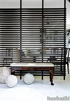 LOUVERED SCREEN – In a retro Houston home, Elizabeth Kennedy and Ray Booth replaced the '60s room divider with a sleek alternative. An antique bench sits against a custom partition, painted in Benjamin Moore's Briarwood. Click through for the entire gallery and for more entryway ideas.