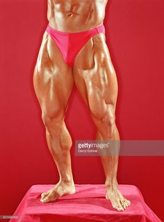 Stock Photo : Bodybuilder standing on podium, red background