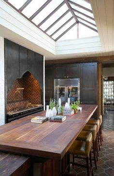 First ...the skylight...a kitchen with a skylight...perfect...    Second...the interesting almost Moorish cut out shape for the range hood. The stove is hand built from France! Whoa.    Third...the massive wood topped island.    Forth...the Saltillo tile floors...something very rustic about these.