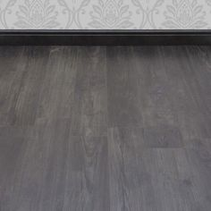 Dark grey tones and a gorgeous wood effect texture make this Manor Nostalgic Teak Graphite laminate floor a must-have for a modern home that requires a striking décor addition at a great price. The embossed surface and the wonderfully reproduced saw marks Wood Floors Wide Plank, House Flooring, Flooring On Walls, Hardwood Floors, Grey Laminate Flooring, Laminate Flooring, Flooring, Hardwood, Flooring Trends
