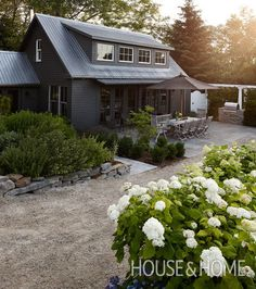 Homeowner and architectural designer Nicolas Lewin painted the exterior of his Chester, Nova Scotia, home a deep grey-green for drama, then added clouds of white blooms curbside for a statement-making contrast. | Photographer: Janet Kimber