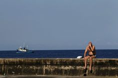 A tourist sunbathes on Havana\'s Malecon. On Saturday nights, packs of friends and sweethearts congregate on the seawall, playing guitar, swilling rum and kissing under the star-speckled sky.