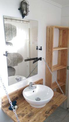 """La nouvelle salle de bain de la bergerie est Composée d'un plan vasque """"façon pont-levis"""", d'éléments trouvés dans les étables et granges du domaine : Vieille porte retapée, arrêt de volet à tête bergère, d'une pentur, d'une vieille lampe et d'une vasque et d'un robinet chiner dans une brocante. L'étagère a été conçu à partir d'une palette de bois récupérée !"""