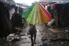 "Child carries umbrella in pouring rain in slum of Susan's Bay in Sierra Leone's capital Freetown (8/22/12). Sierra Leonee's government has described current cholera outbreak in W Africa state as ""national emergency"". At height of wet season, over-populated areas of poor water & sanitation are exacerbating spread of disease. Some 170 deaths are reported since start of year. (photo: 8/22/12, Reuters/Simon Akam)"