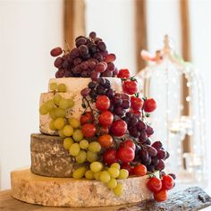 A rustic wedding cake made from rounds of cheese, decorated with grapes and tomatoes.
