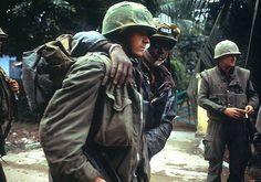 Injured U.S. Marines limping away from the battlefield. The man at left wears an M65 field jacket and a M1941 haversack, while the Marine on the far right of the picture wears a M1952 flak vest.