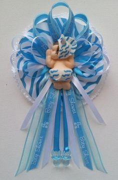 Baby Shower Corsage with baby in teal zebra bonnet and diaper centerpiece