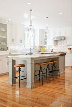 Polished kitchen style, a new favourite. Rangehood, island lights, SUNSHINE, island and flooring....AND glass cabinets.