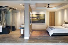 A sculptural fan circulates the air above the master suite's Poliform Arca bed. The painting is by Arthur Okamura. French oak from Sterling Interiors/Design covers the floor here as well as throughout many other spaces in the residence. A wall separates the bedroom from the bath, leaving most of the space open.