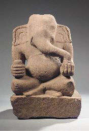 a khmer rose sandstone figure of ganesha circa 11th century Seated with both legs crossed on a rectangular base, his right hand holding tusk, the other with bowl containg sweets, wearing striated dhoti, pot-bellied, his head with curling trunk and large ears 48 cm high