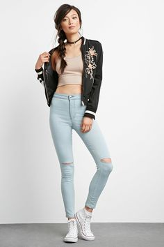 A pair of light wash skinny jeans featuring ripped up knees, a high rise, an ankle length, two patch pockets in back, and a zip fly.
