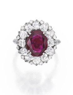 PLATINUM, RUBY AND DIAMOND RING, HARRY WINSTON. Centered by an oval-shaped ruby weighing 2.99 carats, framed by round and pear-shaped diamonds weighing approximately 2.00 carats,  signed Winston.
