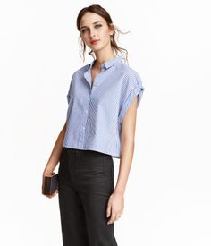Short, straight-cut shirt in airy cotton fabric. Narrow collar, cap sleeves with sewn cuffs, and buttons at front.