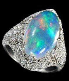 Platinum diamond and opal ring   Oval opal in a filigree setting set with petite round cut diamonds.