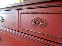 Custom red chalk paint (Olympic Gumball Red & chocolate brown paint mixed with homemade chalk paint). Kona stain as a glaze. Lightly distressed and sealed with wax. Original pulls were sprayed with Oil Rubbed Bronze paint.
