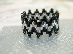 A stunning peyote ring! Made of Japanese delica beads in black and silver.    The ring is approximately 3/8(1,1cm)wide. The size is up to you, it