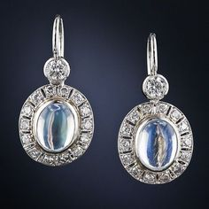 A luminous pair of blue-flash moonstones glow from within sparkling frames of round brilliant-cut diamonds surmounted by a larger bezel-set diamond in these wonderful, wearable Art Deco style earrings, newly crafted in platinum.