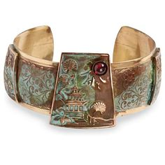 Both necklace and cuff feature a detailed scene of a pagoda among trees and a cabochon garnet accent. Designed by Elaine Coyne, the scrollwork bracelet repeats the pagoda motif twice more. 1 3/8' pendant hangs on brown and olive leather cords that adjust 16'-18' with gold-plated extender chain. 1 3/8' cuff tapers to 1' and fits most wrists. All are hand made in solid brass with hand-applied verdigris patina.