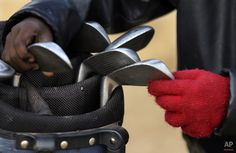 Six-year-old Ntando Gumede, pulls out a chipping iron from a golf bag during a game at a park in Katlehong township, east of Johannesburg, South Africa, Thursday, July 16, 2015. (AP Photo/Themba Hadebe)