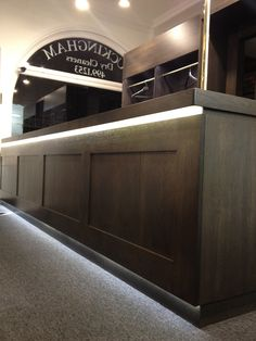 Buckingham Dry cleaners ,Mayfair refit. Lighting highlighted the modern,dark wood panels at the front of the counters