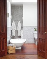Modern Master Bathroom | Martha Stewart Living - Mahogany doors originally from the kitchen were repurposed to create a grand entrance to the en suite master bathroom, which has an egg-shaped Agape tub and Ann Sacks tiles.