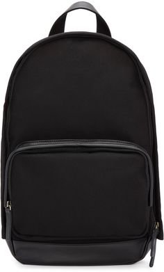 Canvas backpack in black. Tonal leather trim throughout. Carry handle at top. Adjustable shoulder straps. Zippered compartment at face. Two-way zip closure at main compartment. Embossed logo at leather base. Zip pocket and laptop compartment at bag interior. Tonal textile lining. Brass and gunmetal-tone hardware. Tonal stitching. Approx. 12.5